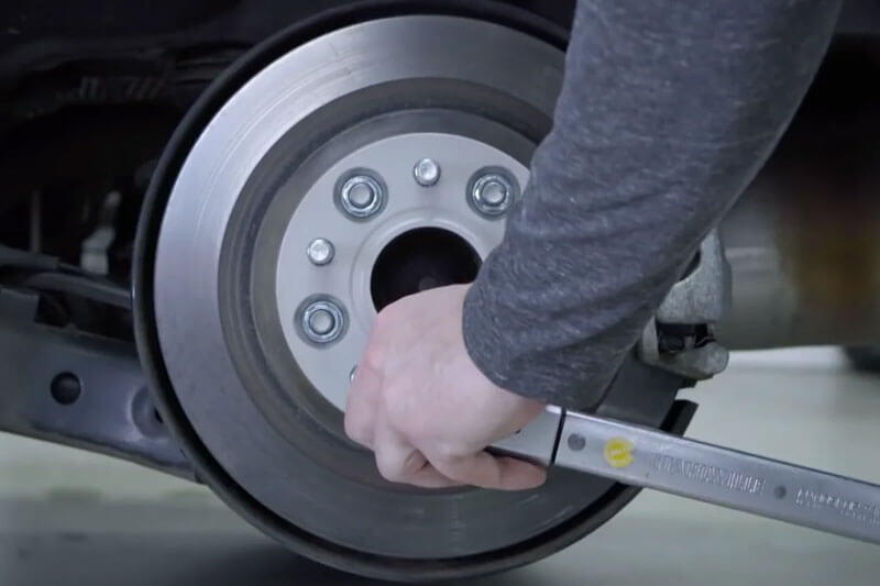 Install the wheel spacer with a torque wrench, observing the order of fastening the bolts opposite one another.